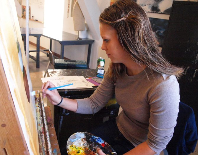 Junior Shayna Mangiaracino works on an oil painting of a birdhouse in one of her art classes last semester.