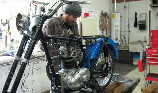 Barnyard Scraps Restoration worker Micah Tracy works on a motorcycle in the Baldwin City workshop. Tracy, along with his brother-in-law Shawn Carlisle, find their supplies by digging through old barns and sheds, as well as by purchasing parts from Craigslist. The brothers-in-law chose Baldwin City as their workshop location due to its proximity to other larger cities.