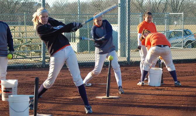 Sophomore Maggie Holmberg keeps her eyes on the ball while taking a swing at practice Monday at Cavaness Field. Holmberg is also one of the team's top returning pitchers from the 2011 season.