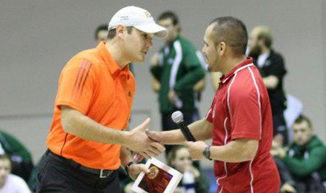 Baker University head track and field coach Zach Kindler, left, accepts his award for winning the Heart of America Athletic Conference Indoor Track and Field Coach of the Year from Graceland University head coach Daniel Alvarado. Kindler coached the men's and women's indoor track and field teams to conference championships.