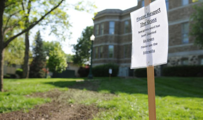 The Baker University maintenance staff encourages students to use the sidewalks, as the grass has been seeded and attempting to grow.