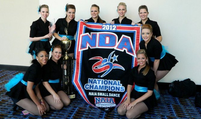 The Baker University dance team poses with its national championship banner and trophy after placing first in the NAIA Small Dance category Friday at the National Dance Alliance Collegiate Championship in Daytona Beach, Fla. From left to right: FRONT ROW: senior Danielle Small, junior Bailey Buchman, sophomore Maddie Kristoffersen and freshman Amanda Seeley. BACK ROW: freshman Brittany Gapter, junior Kristina Shiddell, sophomore Alyssa Staats, freshman London Wise and senior Sarah Pembrook.
