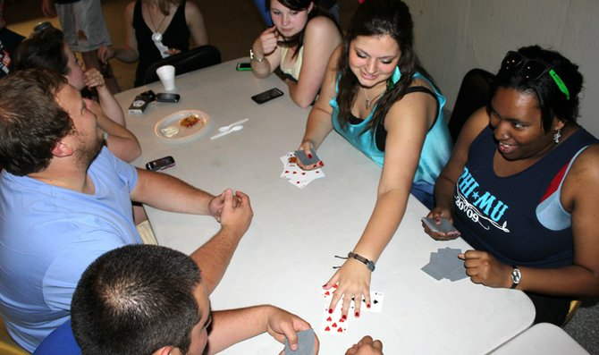 Students play cards Wednesday at Phi Mu's Pizza Palooza at Delta Tau Delta fraternity house. Pizza Palooza was started by Baker University's Zeta Alpha chapter of Phi Mu sorority. Delta Tau Delta and Phi Mu raised $225, or about $112, for each of their philanthropies, juvenile diabetes research and Children's Miracle Network, respectively.