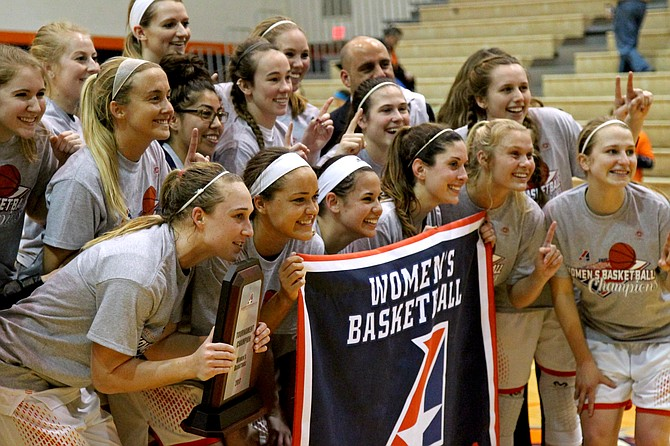 The Baker women's basketball players pose for a photo with their Heart championship banner after defeating Benedictine 64-51. The team won its first-ever Heart Conference Tournament title along with the regular-season championship.